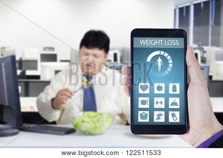 Picture of overweight businessman eats salad and refuse junk food shot with weight loss application on the mobile phone screen