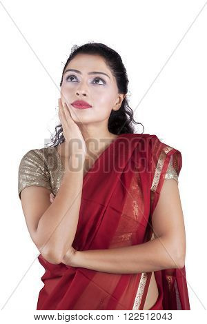 Portrait of young indian woman thinking and looking up while wearing traditional clothes in the studio