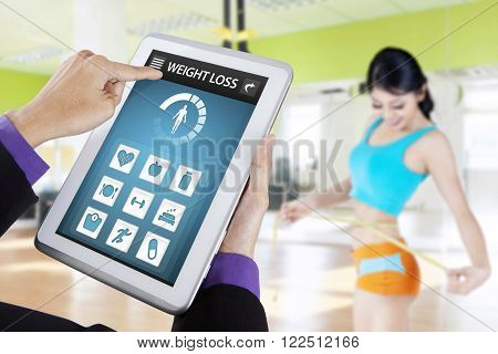 Close up of weight loss applications on the tablet screen and young woman measures her waist at fitness center