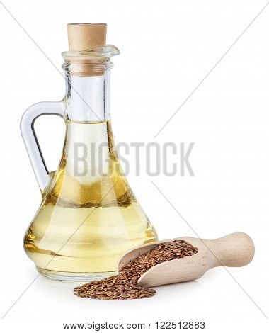 Linseed oil in glass bottle and flax seeds in wooden scoop isolated on white background