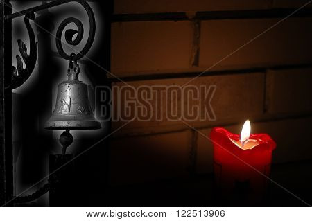 Picture shows old rustic light with a churchbell around the corner with a shadow from a candle light. Background is a brick wall.