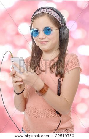 preteen girl listening to music with his smartphone, bokeh background