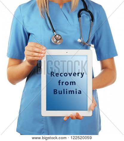 Female doctor with tablet pc and text Recovery from Bulimia on screen isolated on white