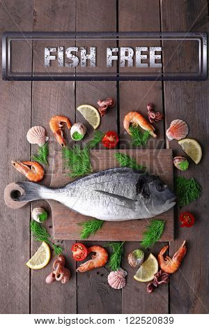 Dorado fish and other ingredients and fish free sign on wooden table, top view