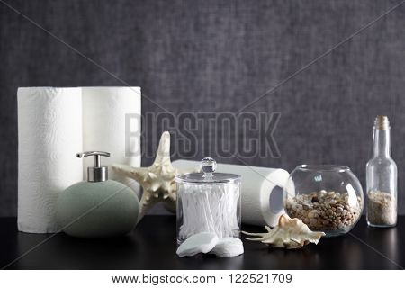 Bathroom set with towels, sponges and dispenser on grey background