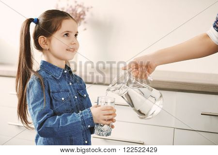 Little girl holding glass and adult woman pouring water from jug in living room