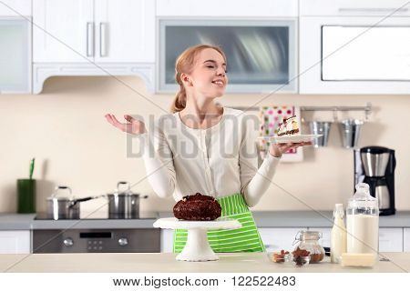 Young woman holding a piece of chocolate cake on a plate
