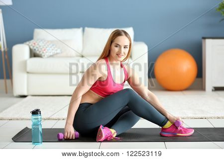 Young sportswoman sitting with dumbbells and bottle of water on mat at home