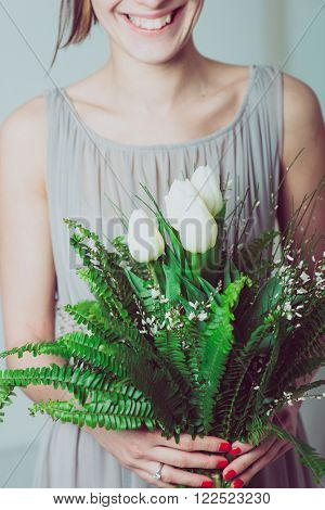 Close up image of smiling bridesmaid with a bouquet of tulip flowers