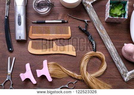 Frame with strand of hair, barber tools, equipment and cosmetics on wooden background