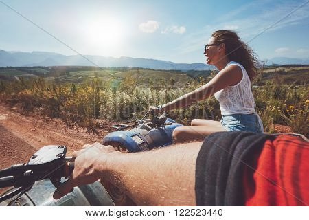 Young people driving quad bikes on a summer day. Woman enjoying country ride on an all terrain vehicle. POV shot.