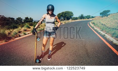 Full length portrait of young woman standing on a countryside highway with a longboard.