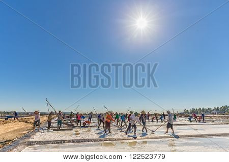 Binh Thuan, Vietnam - January 22nd, 2016: Group Fishermen rhythmic scraping salt heaps, above the radiating sun shines for stars such as fishermen in morning coastal location of Binh Thuan, Vietnam