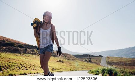 Happy young woman walking with a longboard on countryside road. Professional skater outdoors on a sunny day.