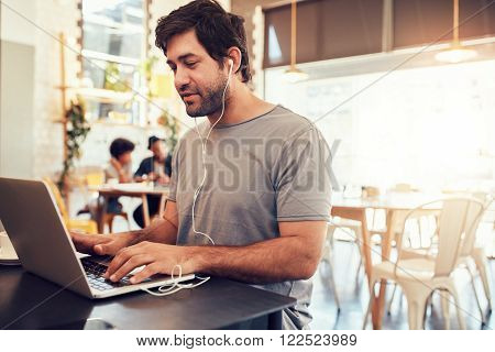 Portrait of handsome young man with earphones working on laptop while sitting at a coffee shop. Young guy at a cafe surfing internet on laptop.