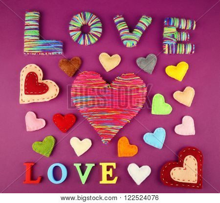Love word with varicolored hearts on purple background