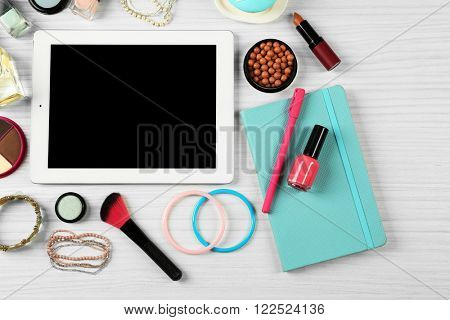 Digital tablet with woman's accessories on white wooden table background, top view