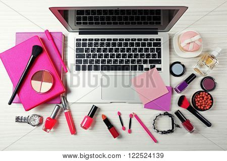 Laptop with woman's accessories on white wooden table background