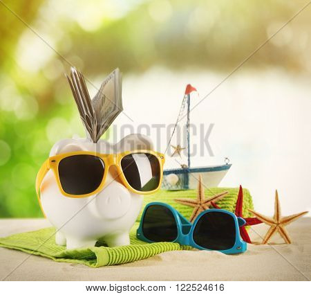 Piggy bank with dollar banknotes, towel and sunglasses on a sand. Holiday money concept