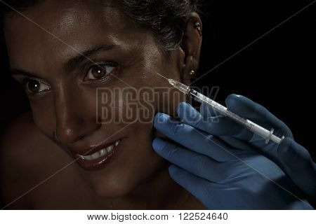 beautiful young female face and hands in gloves with beauty treatment injection isolated on darkness