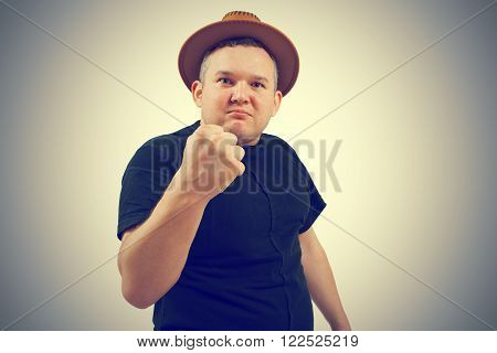 Gangster in hat angry man holding fists against. Isolated on background