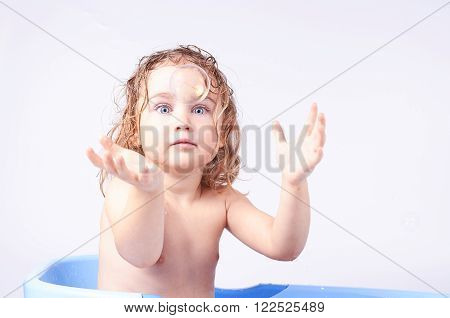 little girl in blue tub catches soap bubble