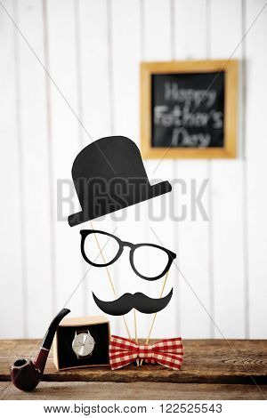 Happy Father's Day inscription at blackboard with bow tie, pipe and watch on wooden table
