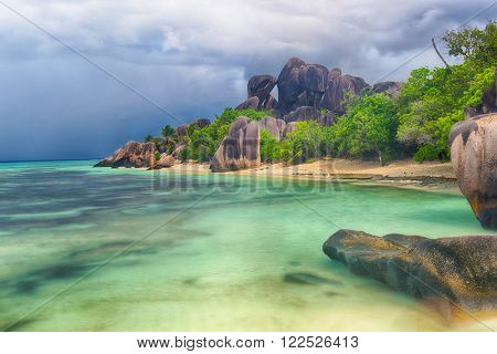 Beautifully shaped granite boulder in the sea of Seychelles at Anse Source d'Argent beach taken with a long exposure. Dramatic stormy sky