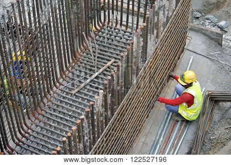 JOHOR, MALAYSIA - MARCH 03, 2015: Construction workers fabricating pile cap steel reinforcement bar at the construction site.