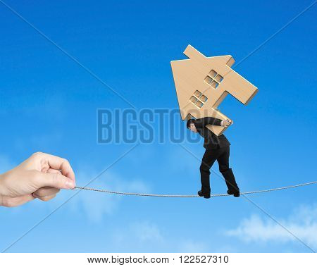 Man carrying wooden house and balancing on tightrope with blue sky background.