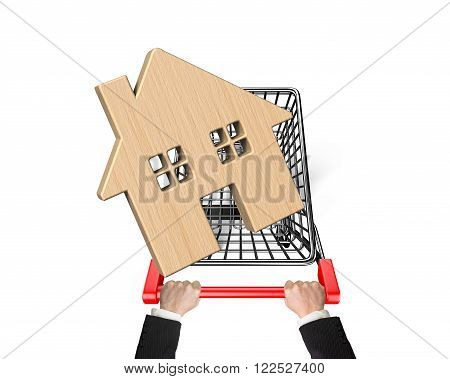 Human hand pushing shopping cart with wooden house isolated on white.