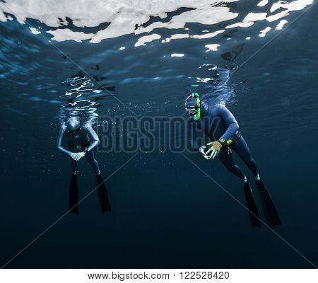 Two free divers preparing for the dive, relaxing on the surface