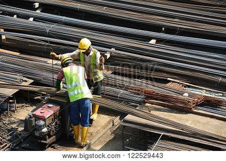JOHOR, MALAYSIA - JANUARY 23, 2016: Construction workers working at the steel bar bending yard in the construction site.