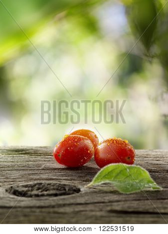 close up view of nice fresh cherry tomatoes on wooden table