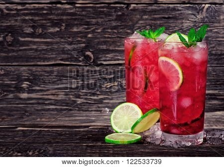 two red cocktail with mint lime and ice on dark wooden background with space for your text