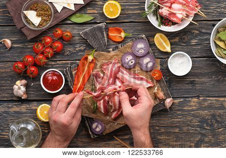 male preparing skewers of grilled bacon. Top view