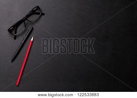 Office leather desk table with pen, pencil and eyeglasses. Top view with copy space