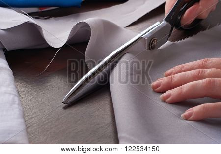 Closeup of a dressmaker cuts scissors cloth in studio
