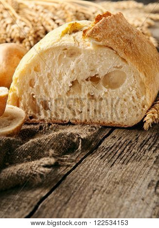 loaf of homemade freshly baked bread and wheat ears on a wooden table in a bakery