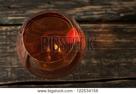 vintage cognac in large round glass on the old wooden background closeup. Top view with copy space