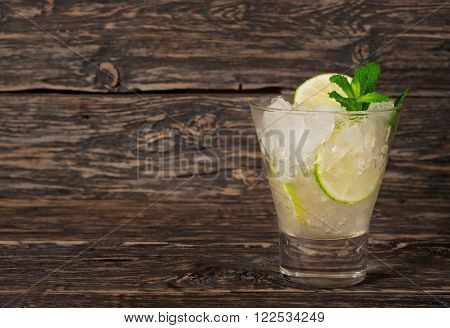 cocktail with white rum or gin with ice lime and mint on a dark wooden background with copy space. Summer cocktails background
