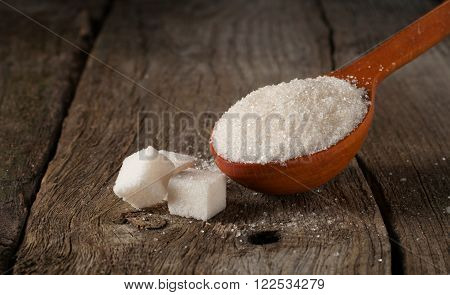 white sugar in wood spoon with sugar cubes closeup on wood table with copy space