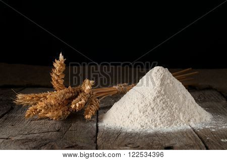 handful of wheat flour closeup with wheat ears on the wooden table