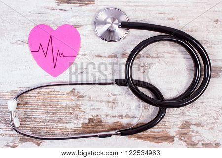 Pink heart of paper with electrocardiogram line and medical stethoscope on old wooden rustic background ecg heart rhythm medicine and healthcare concept
