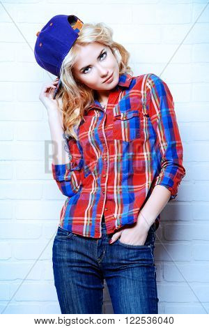 Beautiful modern girl with curly blonde hair wearing jeans and casual shirt posing by a brick wall.