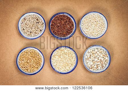 Variety of grain rice in cup on natural brown paper background ; coarse red and white rice , millet ,barley , wheat, oat seed