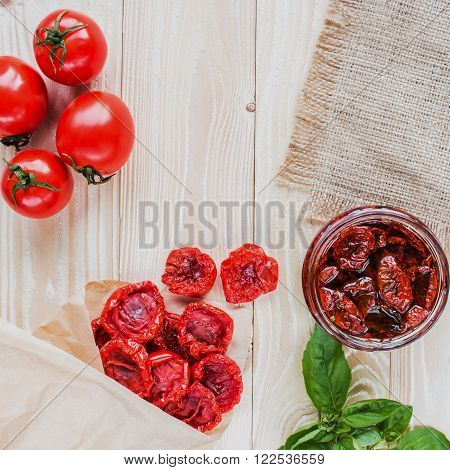 dried tomatoes in an envelope of kraft paper on a wooden table covering of sackcloth. top view. copy space