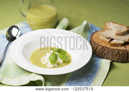 Soup of green vegetables with fresh herbs and cottage cheese