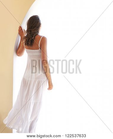 Young woman in a wite dress chilling in a resort at summer.