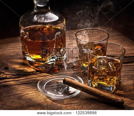 Glasses of whiskey with smoking cigar on wooden table
